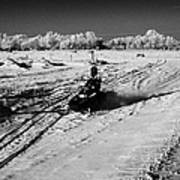 two men on snowmobiles crossing frozen fields in rural Forget Saskatchewan Canada Poster