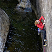 Woman Climbing Above A River Poster