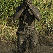 A Participant Wipes Mud From His Face Poster