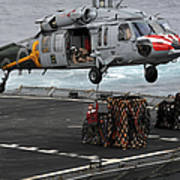 A Sailor Hooks Cargo To An Mh-60s Sea Poster