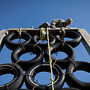 A Soldier Climbs Over A Tire Tower Poster