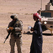 A Soldier Communicates With A Local Poster