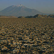 A Volcano Rises Above A Dry Lake Bed Poster