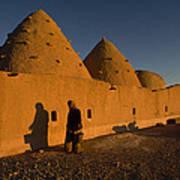 A Woman Walks Past A Sunlit Mud Brick Poster