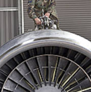 Airman Checks Components Atop A C-5 Poster