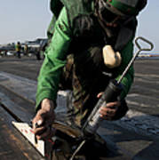 Airman Greases The Catapult Shuttle Poster