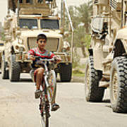 An Iraqi Boy Rides His Bike Past A U.s Poster by Stocktrek Images