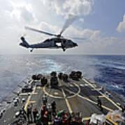 An Mh-60r Sea Hawk Transfers Supplies Poster