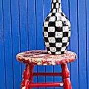 Blach And White Vase On Stool Against Blue Wall Poster