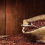 Burlap Sack Of Coffee Beans Against Dark Wood Poster by Sandra Cunningham