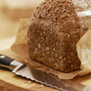 Close Up Of Knife And Loaf Of Bread In Wrapper Poster