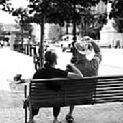 Couple Resting On A Downtown Bench On A Windy Day Poster