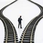 Figurine Between Two Tracks Leading Into Different Directions  Symbolic Image For Making Decisions Poster by Bernard Jaubert