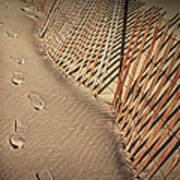 Footprints On The Beach Along A Fence Poster