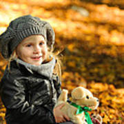 Little Girl In Autumn Leaves Poster