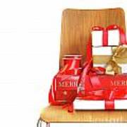 Pile Of Gifts On Wooden Chair Against White Poster