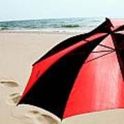 Red And Black Umbrella On The Beach With Footprints Poster