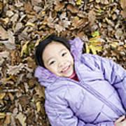 Smiling Girl Lying On Autumn Leaves Poster