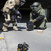 Soldiers Dressed In Bomb Suits Examine Poster