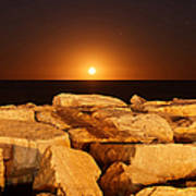 The Moon Rising Behind Rocks Lit Poster