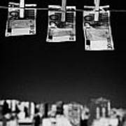 Three Twenty Euro Banknotes Hanging On A Washing Line With Blue Sky Over City Skyline Poster