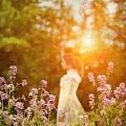 Woman Staning Sideways In Garden At Sunset Poster