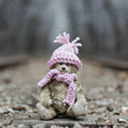 Little Teddy Bear Sitting In Knitted Scarf And Cap In The Winter Forest Between The Rails Poster
