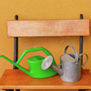 A Watering Can Of  Aluminium And A Plastic One Laid On Wooden Bench Poster