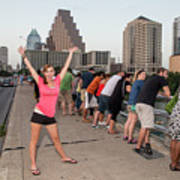 Cheerful Attractive Female Austinite Waves Her Hands With Excitement On Seeing The Austin Bats Poster