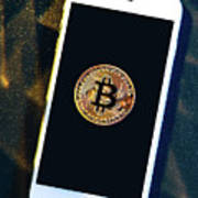 Phone With A Bitcoin Laying On Top Of It. Poster
