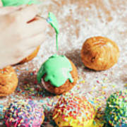 Woman's Hand Coating A Donut With Green Frosting. Poster