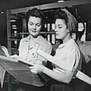 Two Women In Workshop Looking At Poster