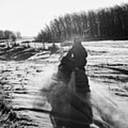 man on snowmobile crossing frozen fields in rural Forget Saskatchewan Canada Art Print by Joe Fox