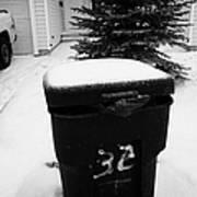bag sticking out of litter waste bin covered in snow outside house in Saskatoon Saskatchewan Canada Art Print