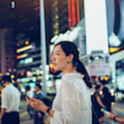 Beautiful Asian woman using mobile phone while crossing road in busy downtown city street at night Art Print