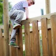 Boy Climbing Over Wooden Fence Art Print