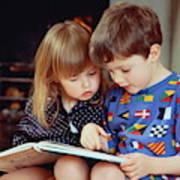 Boy(4-5)and girl(2-3)sat by fire in pyjamas reading book together Art Print