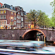 Canal Bridge And Boat Tour In Amsterdam At Evening Art Print