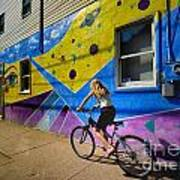 Girl Rides Bicycle Past Mural On The South Side Of Pittsburgh Print by Amy Cicconi