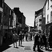 pedestrians walking down closed pedestrian area of quay street on sunny sunday afternoon Galway city Art Print