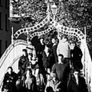 People Crossing The Hapenny Ha Penny Bridge Over The River Liffey In Dublin At A Busy Time Art Print
