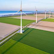 Wind turbines lined up along coast towards industrial area Art Print