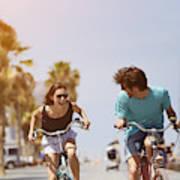 Woman chasing man while riding bicycle Art Print