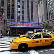Yellow Cabs Pass In Front Of Radio City Music Hall Art Print