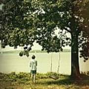 Young Boy Looking Out At The Water Under A Big Tree Art Print