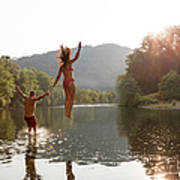 Young Couple Jumping Into River Art Print