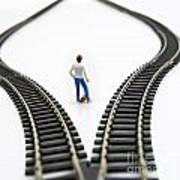 Figurine Between Two Tracks Leading Into Different Directions Symbolic Image For Making Decisions. Art Print