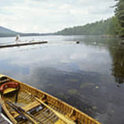 A Canoe Floats Next To A Dock Art Print by Skip Brown