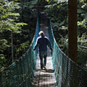 A Man Walks Across A Suspension Bridge Print by Taylor S. Kennedy