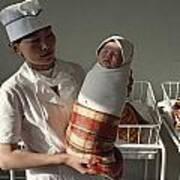 A Nurse Holds A Tightly Wrapped Newborn Art Print